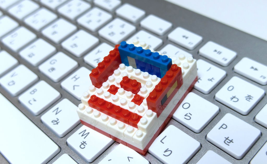 A red face in a white rectangle made of nanoblocks, resting on a silver Apple keyboard.
